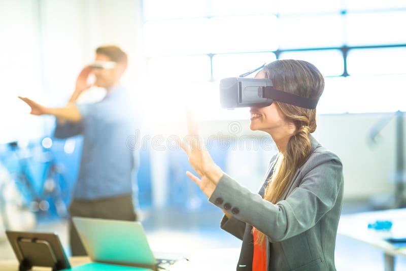 Kvinnlig grafisk formgivare som använder virtuell verklighethörlurar med mikrofon arkivbild