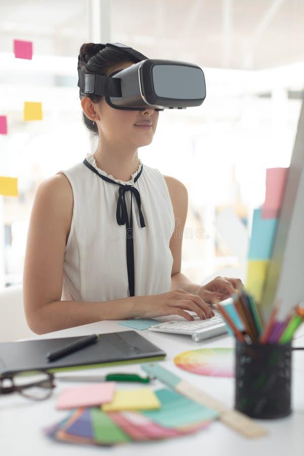 Kvinnlig grafisk formgivare som använder virtuell verklighethörlurar med mikrofon, medan arbeta på datoren på skrivbordet royaltyfria bilder