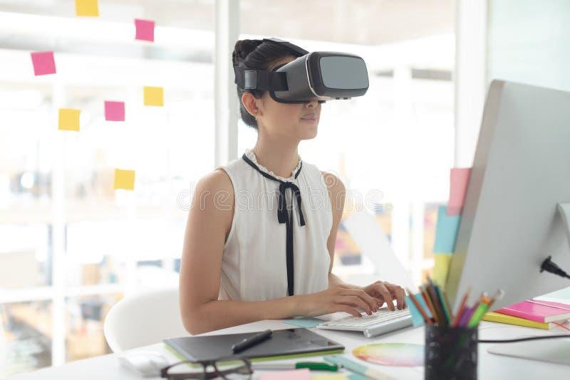 Kvinnlig grafisk formgivare som använder virtuell verklighethörlurar med mikrofon, medan arbeta på datoren på skrivbordet royaltyfria foton