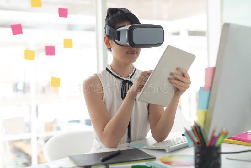Kvinnlig grafisk formgivare som använder virtuell verklighethörlurar med mikrofon och den digitala minnestavlan på skrivbordet arkivfoto