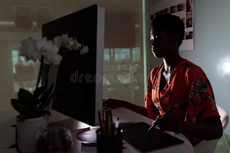 Kvinnlig grafisk formgivare som anv?nder den grafiska minnestavlan p? skrivbordet royaltyfria foton