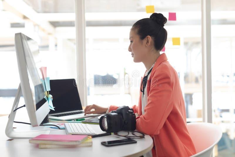 Kvinnlig grafisk formgivare som arbetar på bärbara datorn på skrivbordet i ett modernt kontor royaltyfria foton