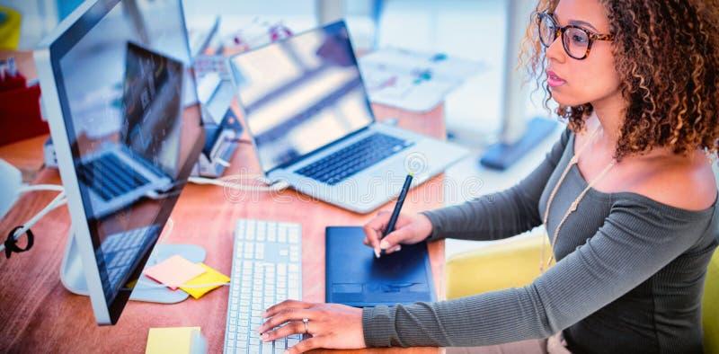 Kvinnlig grafisk formgivare som arbetar på datoren, medan genom att använda den grafiska minnestavlan på skrivbordet royaltyfri fotografi