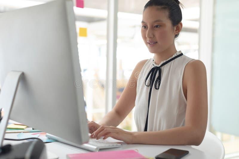 Kvinnlig grafisk formgivare som arbetar på datoren på skrivbordet i ett modernt kontor royaltyfria foton