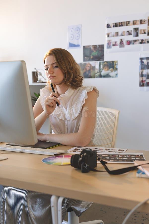 Kvinnlig grafisk formgivare som arbetar p? den diagramminnestavlan och datoren p? skrivbordet royaltyfri foto