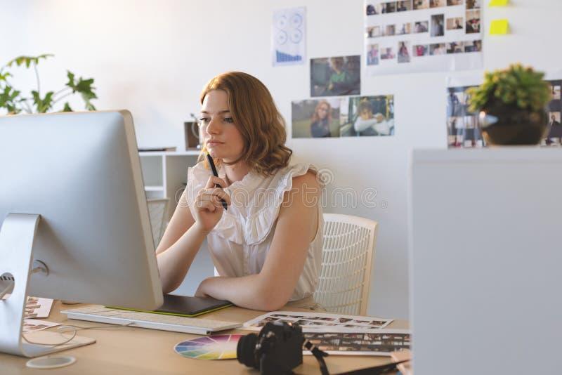 Kvinnlig grafisk formgivare som arbetar p? den diagramminnestavlan och datoren p? skrivbordet arkivfoton