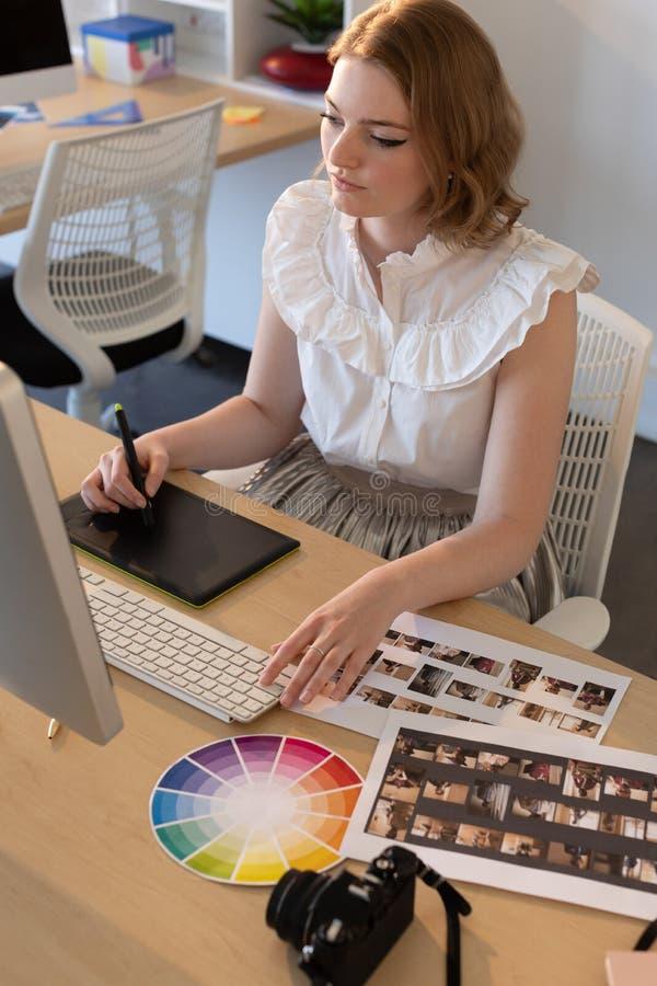 Kvinnlig grafisk formgivare som arbetar p? den diagramminnestavlan och datoren p? skrivbordet arkivbild