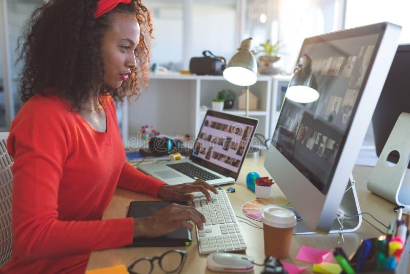 Kvinnlig grafisk formgivare som arbetar p? skrivbords- PC p? skrivbordet arkivfoto