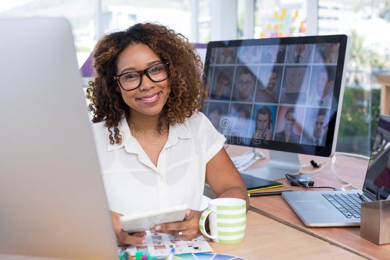Kvinnlig grafisk formgivare som i regeringsställning använder den digitala minnestavlan fotografering för bildbyråer