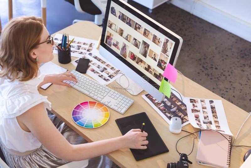 Kvinnlig grafisk formgivare som i regeringsställning arbetar på den grafiska minnestavlan och datoren på skrivbordet royaltyfri bild
