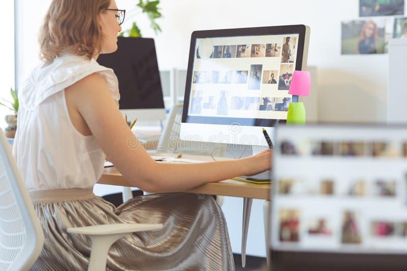 Kvinnlig grafisk formgivare som i regeringsställning arbetar på den grafiska minnestavlan på skrivbordet arkivbilder
