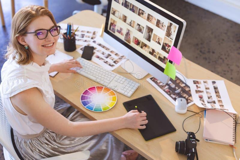 Kvinnlig grafisk formgivare som i regeringsställning arbetar på den grafiska minnestavlan på skrivbordet arkivfoto