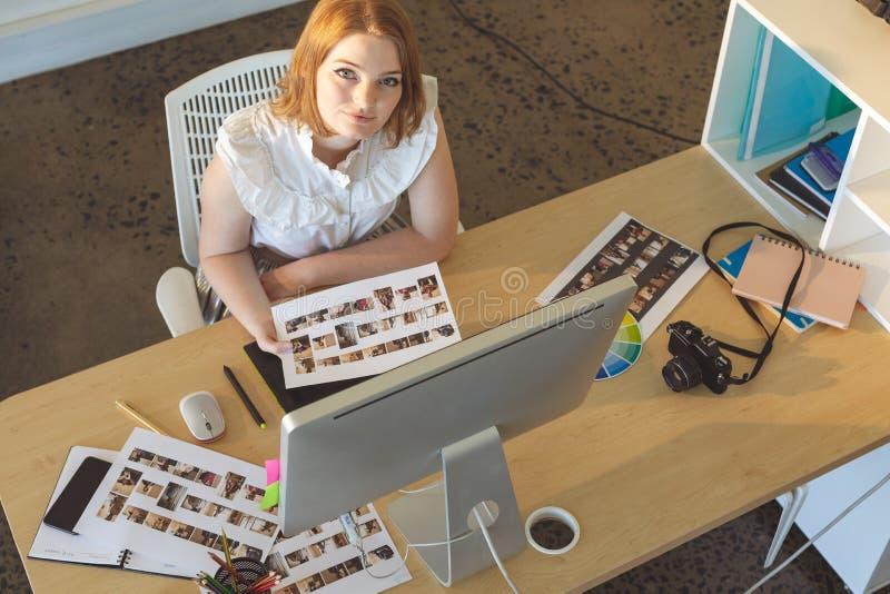 Kvinnlig grafisk formgivare som i regeringsställning arbetar på skrivbordet royaltyfri bild