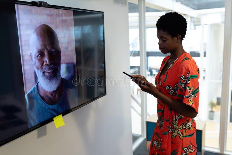 Kvinnlig grafisk formgivare som i regeringsställning gör den videopd appellen till affärspartnern arkivfoto