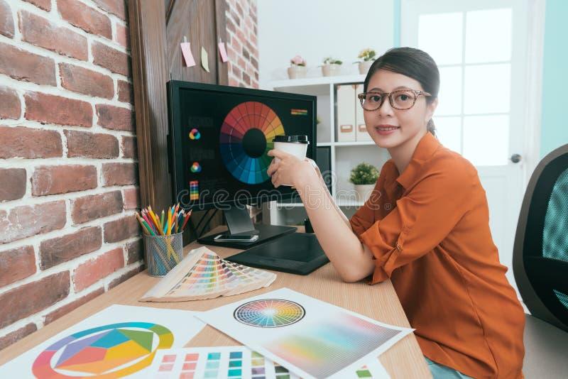 Kvinnlig grafisk formgivare som rymmer den varma kaffekoppen royaltyfria foton