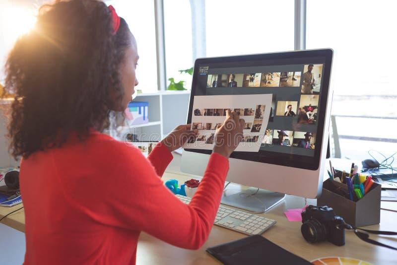 Kvinnlig grafisk formgivare som ser fotografier royaltyfria foton