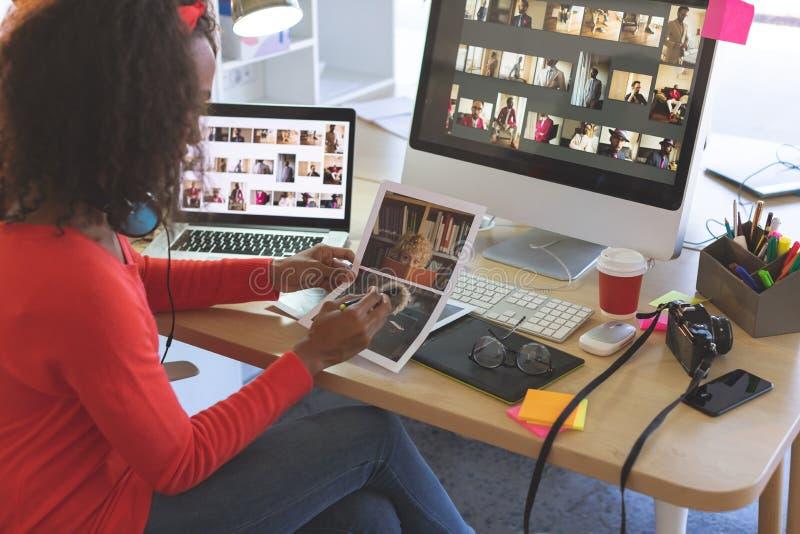 Kvinnlig grafisk formgivare som ser fotografier på skrivbordet arkivbilder