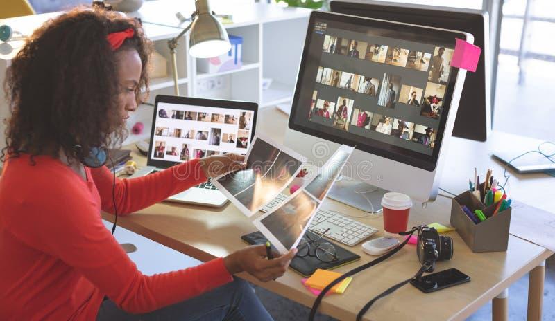 Kvinnlig grafisk formgivare som ser fotografier p? skrivbordet arkivfoton