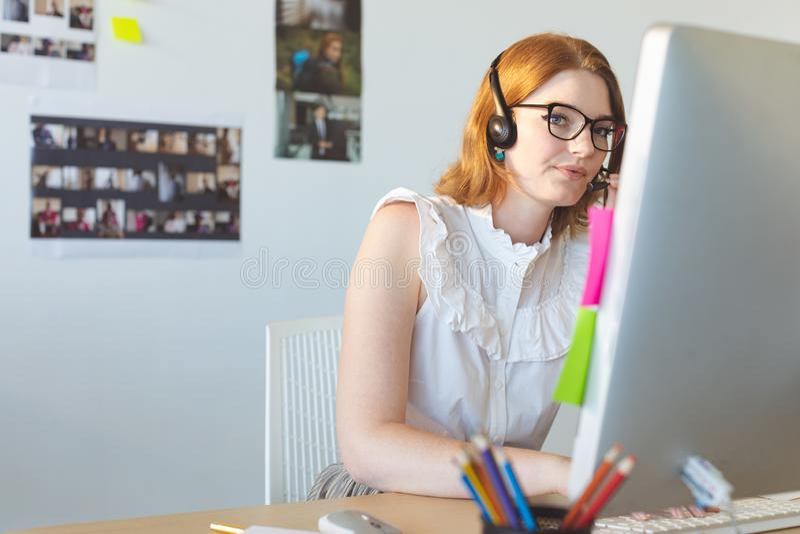 Kvinnlig grafisk formgivare som talar p? headphonen, medan arbeta p? datoren p? skrivbordet royaltyfri foto
