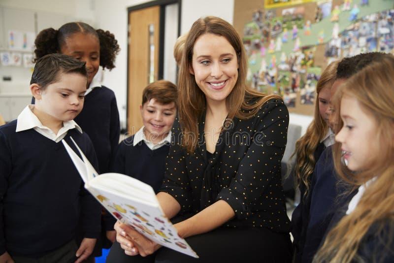 Kvinnlig grundskola för barn mellan 5 och 11 årlärare som ser till en grupp av skolaungar som står runt om henne, som hon läser t arkivbild
