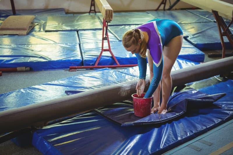 Kvinnlig gymnast som applicerar kritapulver på hennes händer, innan övning arkivfoto