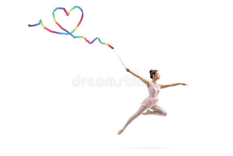 Kvinnlig gymnast som g?r en hj?rtaform med ett band royaltyfri fotografi