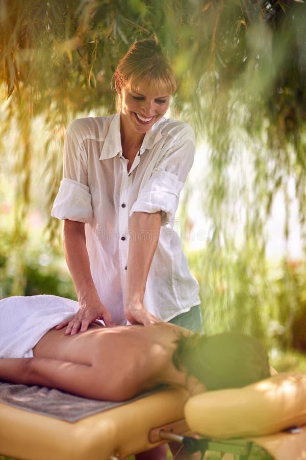 Kvinnlig häleribaksidamassage från en massageprofessionell på beaen royaltyfria foton