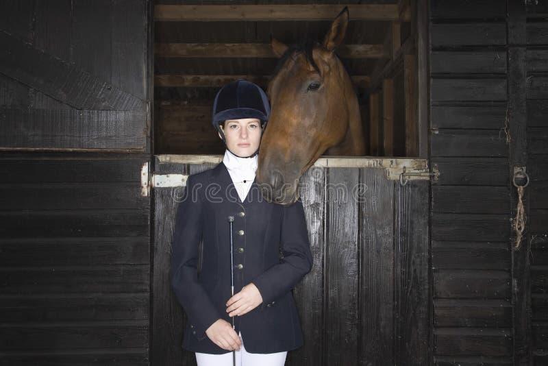 Kvinnlig hästrygg Rider With Horse In Stable royaltyfri bild