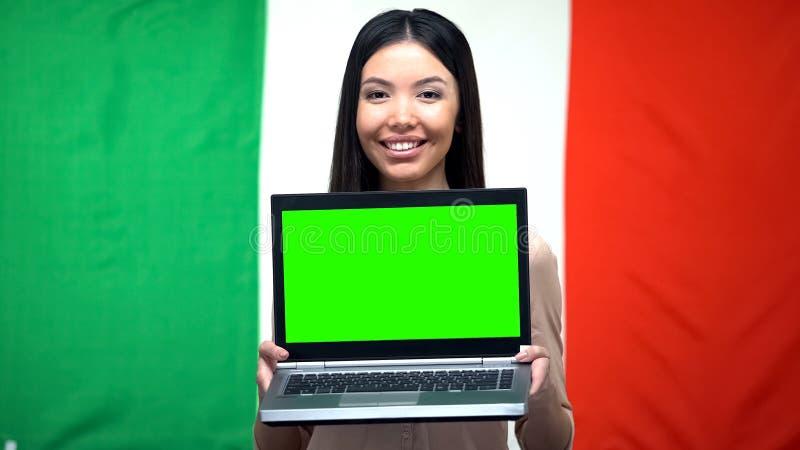 Kvinnlig hållande bärbar dator med den gröna skärmen, italiensk flagga på bakgrund, emigration arkivbild