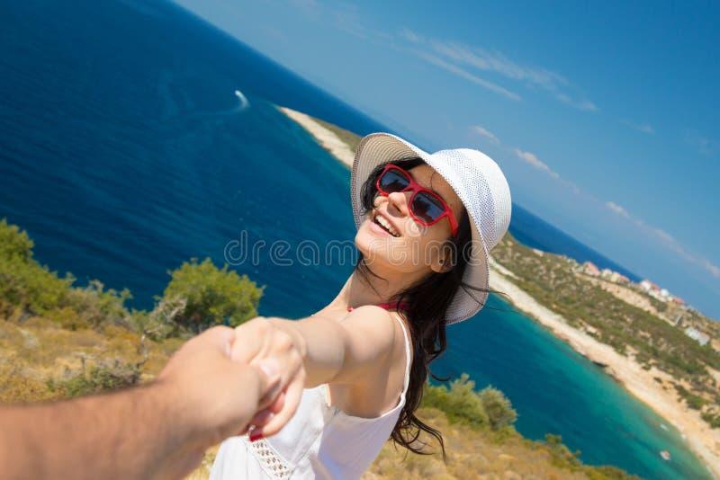 Kvinnlig hållande man'shand Härligt hav i bakgrunden fotografering för bildbyråer