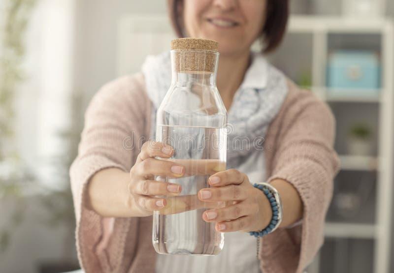 Kvinnlig hållande vattenflaska i kök arkivfoton