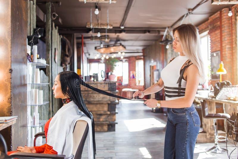 Kvinnlig hårskänk som arbetar på att utforma en kvinnas hår Frisör i ett lyckligt lynne, medan arbeta på en stil för hår för kvin royaltyfri foto