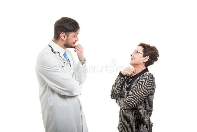 Kvinnlig hög patient som talar med den manliga doktorn arkivbild