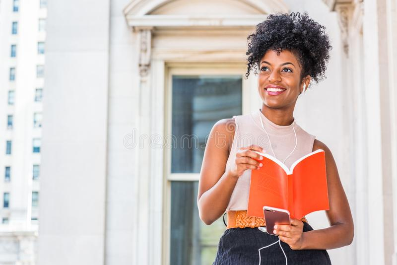 Kvinnlig högskolestudent för ung lycklig afrikansk amerikan med den afro frisyren som sitter med tappningstilkontorsbyggnad i New arkivbilder