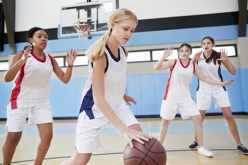 Kvinnlig högstadiumbasket Team Dribbling Ball On Court fotografering för bildbyråer