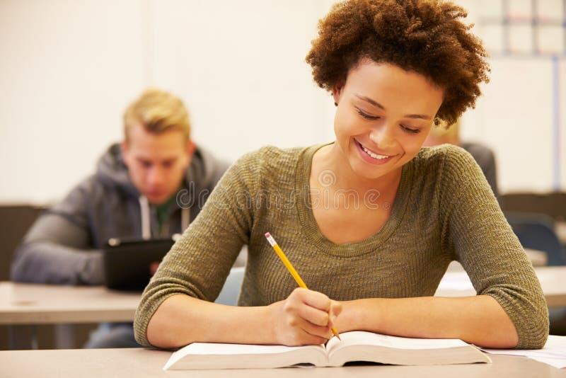 Kvinnlig högstadiumstudent Studying At Desk i klassrum royaltyfri fotografi