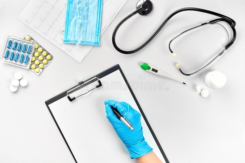 Kvinnlig hand för doktors` s i blåa handskar som fyller sjukdomshistorien på den vita tabellen arkivbild