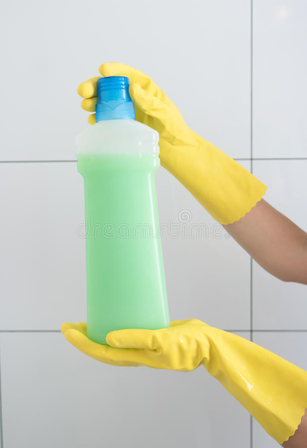 Kvinnlig hand i en rubber handskeinnehavflaska med tvättmedel royaltyfri bild