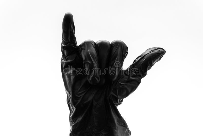 Kvinnlig hand i svarta handskeshowgester, tecken och symboler som isoleras på vit bakgrund Två fingrar som ut klibbar och visar royaltyfri bild