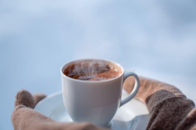 Kvinnlig hand i tumvanten som rymmer koppen med varmt kaffe slitage vit vinter för härlig stående för begreppsklänningflicka arkivbild