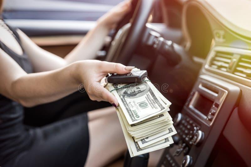 Kvinnlig hand inom erbjudande tangenter och dollar för bil arkivbild