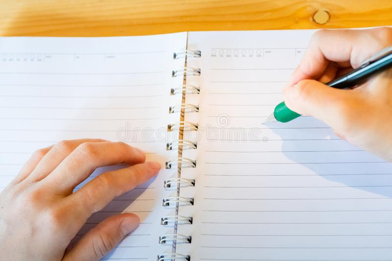 kvinnlig hand med blyertspennahandstil p? anteckningsboken p? coffee shop kvinna som arbetar vid handhandstil p? brevpapper p? tr arkivfoto