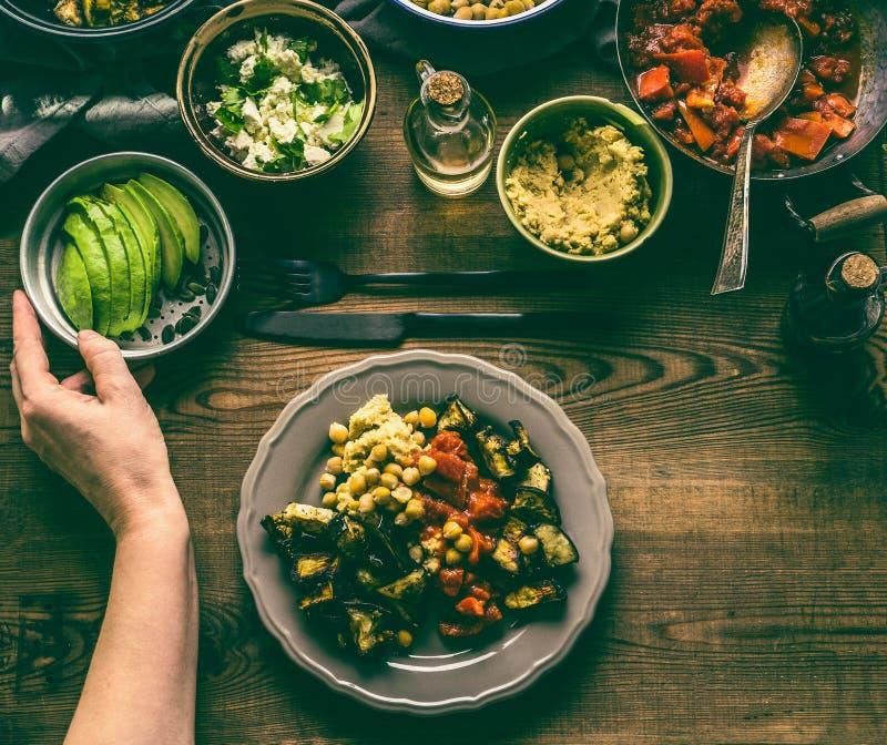 Kvinnlig hand med den sunda vegetariska bunken med den olika grillade grönsaker, avokadot och kikärten arkivfoto