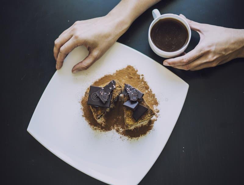 Kvinnlig hand med en kopp kaffe och en härlig chokladkaka fotografering för bildbyråer