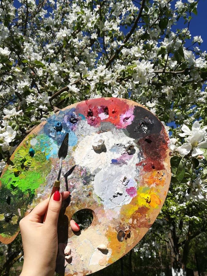Kvinnlig hand med en palettkniv och en palett för målarfärger mot bakgrunden av att blomstra äppleträd arkivfoto