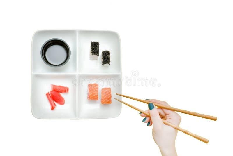 Kvinnlig hand med pinnar och plattan med sushi på en gulingbac fotografering för bildbyråer