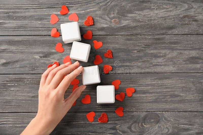 Kvinnlig hand med tomma kuber och röda hjärtor på träbakgrund arkivfoton