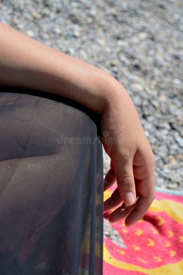 Kvinnlig hand och ben på stranden fotografering för bildbyråer