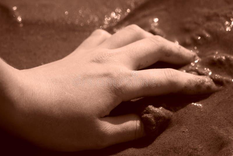 Kvinnlig hand på våt sand fotografering för bildbyråer