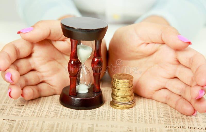 Kvinnlig hand' s med timglas och myntet royaltyfri fotografi